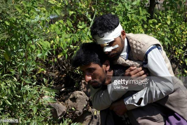 Kashmiri villager Rafik Bagi is carried by his brother Rashid up to his home from the hospital October 12 2005 in the mountain village of Kamel Kut...