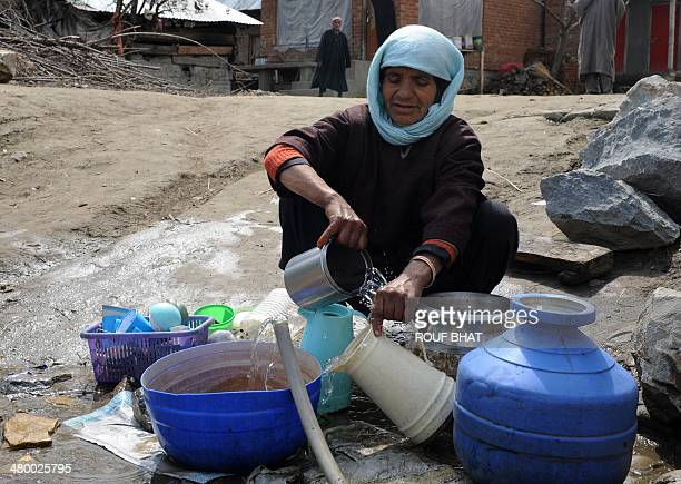A Kashmiri villager washes dishes at the roadside on World Water Day through Hirnaar some 35 kms from Srinagar on March 22 2014 International World...