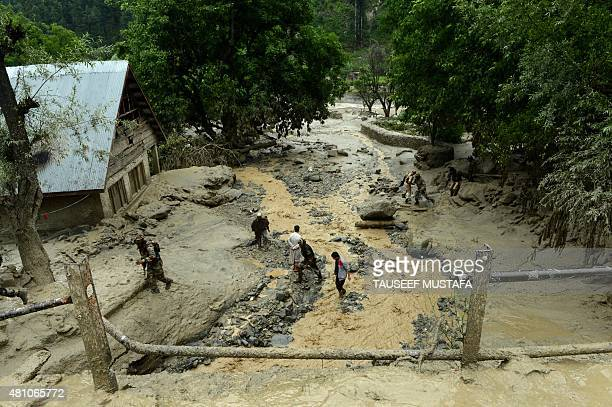 Kashmiri villagers and Indian army soldiers make their way through the mud following flash floods triggered by heavy rainfall at Kullan village about...