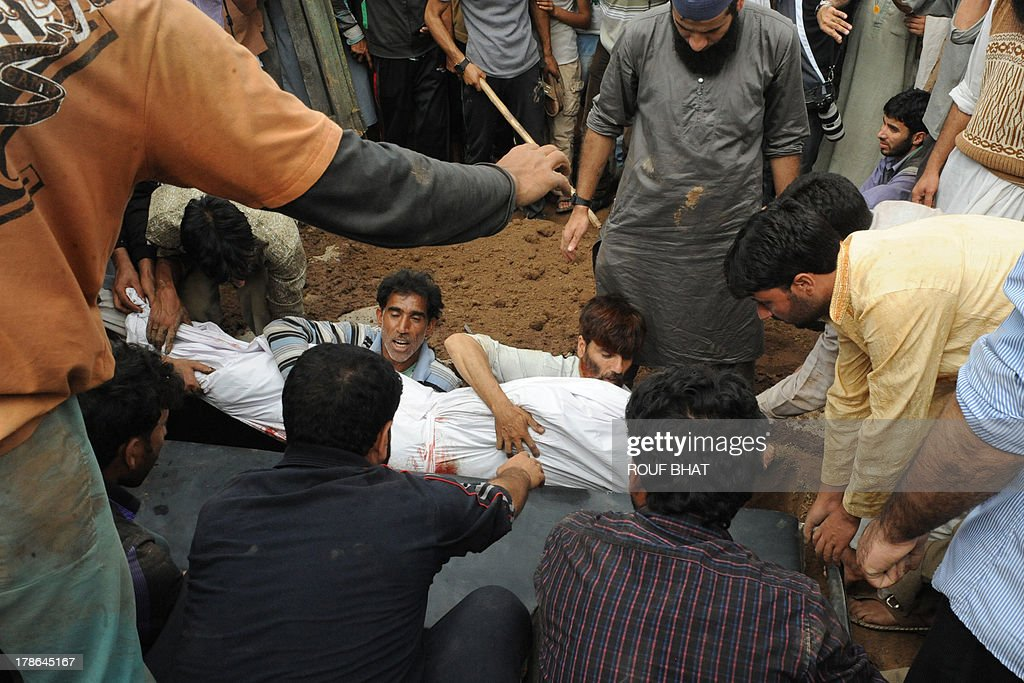 Kashmiri villagers bury a suspected militant during a funeral at Kangan on August 30, 2013. Indian police and troops killed five suspected rebels in an overnight gun battle August 30 in a forested area of northern Kashmir, triggering anti-India protests by local residents, police said. Police and an army contingent began a joint operation around midnight near the Najwan forests, 35 kilometres (20 miles) north of Srinagar, the summer capital of Indian-administered Kashmir. AFP PHOTO/Rouf BHAT