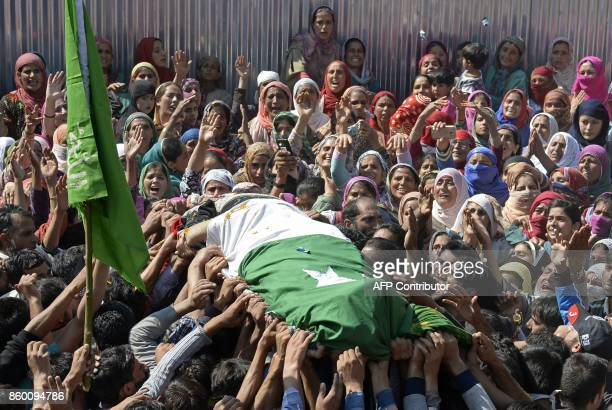 Kashmiri villagers carry the body of a slain militant Nasarullah Mir during his funeral at Hajin village in Bandipora district north of Srinagar on...