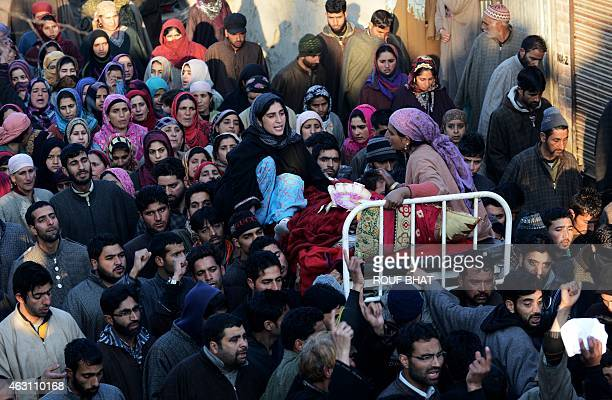 Kashmiri villagers carry the body of Farooq Ahmed Bhat during his funeral in the Palhallan area of Baramulla district on February 10 2015 Bhat was...