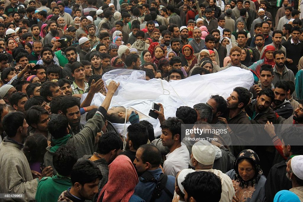 Kashmiri villagers carry the coffin of an Army soldier Mushtaq Ahmad Mir draped in an National flag during his funeral at Qazipora Chadoora district, on May 20, 2014 in Srinagar, India. Mushtaq Ahmad Mir, an Army soldier who was killed in an encounter at Chadoora yesterday. An Army soldier was killed and three others injured in an ongoing encounter at Chadoora in district Budgam of central Kashmir. Sources said that militants managed their escape from the spot and forces were now extending the cordon to more areas.