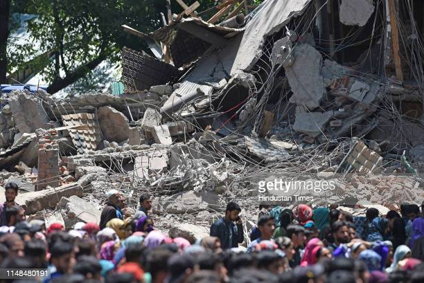 Kashmiri villagers inspect damage to a house where four JaisheMohammad militants including two special police officers who had deserted recently were...