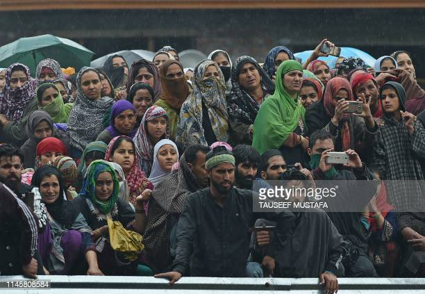 Kashmiri villagers look at a funeral procession of top militant commander Zakir Musa of Ansar Ghazwat-ul-Hind group, which claims affiliation with...