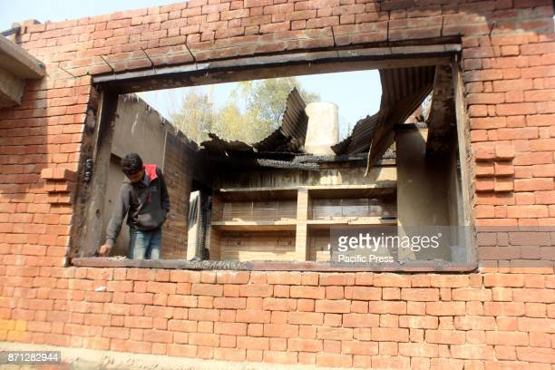 Kashmiri villagers look for belongings at the damaged houses wherein three top Jaish Rebels and Indian Army man killed during an encounter between...