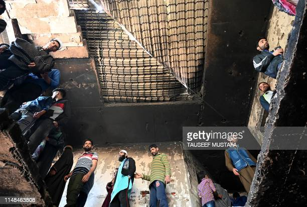 Kashmiri villagers look inside a damaged house following a gunfight between militants and Indian government forces at Panjran village in Pulwama...