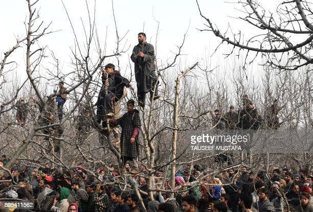 TOPSHOT Kashmiri villagers look on during the funeral procession of militant Tanveer Ahmed at Batmurran Kellar village in Shopian on December 19 2017...