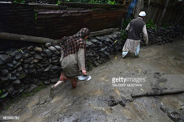 Kashmiri villagers make their way through the mud following flash floods triggered by heavy rainfall at Kullan village about 25 kms northeast of...