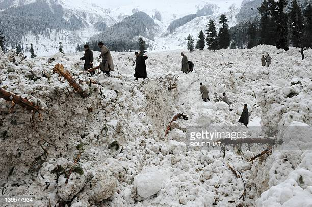Kashmiri villagers search for their belongings after their huts were buried under snow due to avalanche at Ramwari some 70 km from summer capital...