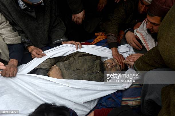 Kashmiri villagers surround the body of alleged Hizbul Mujahideen militant Abid Ahmed during his funeral in Shopian some 60 kms south of Srinagar on...