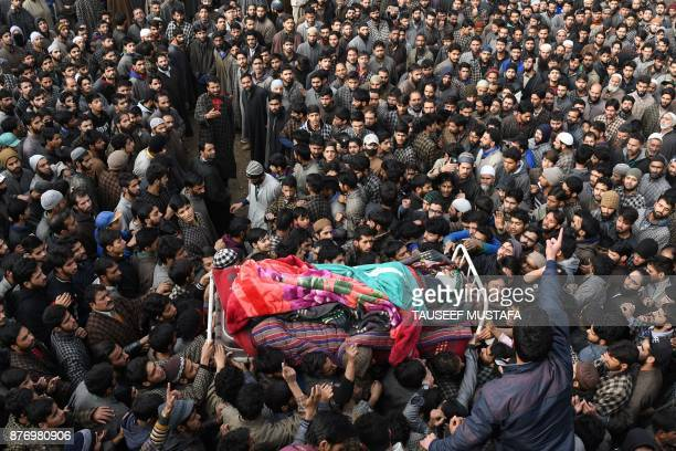 TOPSHOT Kashmiri villagers surround the body of militant Adil Chopan during his funeral procession in Lurow Tral on November 21 2017 Adil was killed...