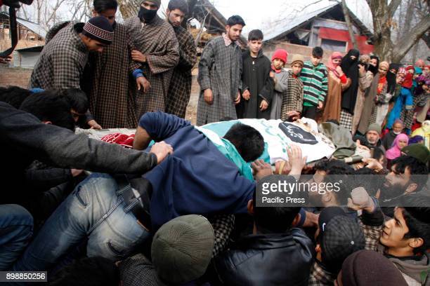 Kashmiri villagers surround the body of top militant commander Noor Mohammad Tantray during his funeral in the Aripal village of Tral district on...