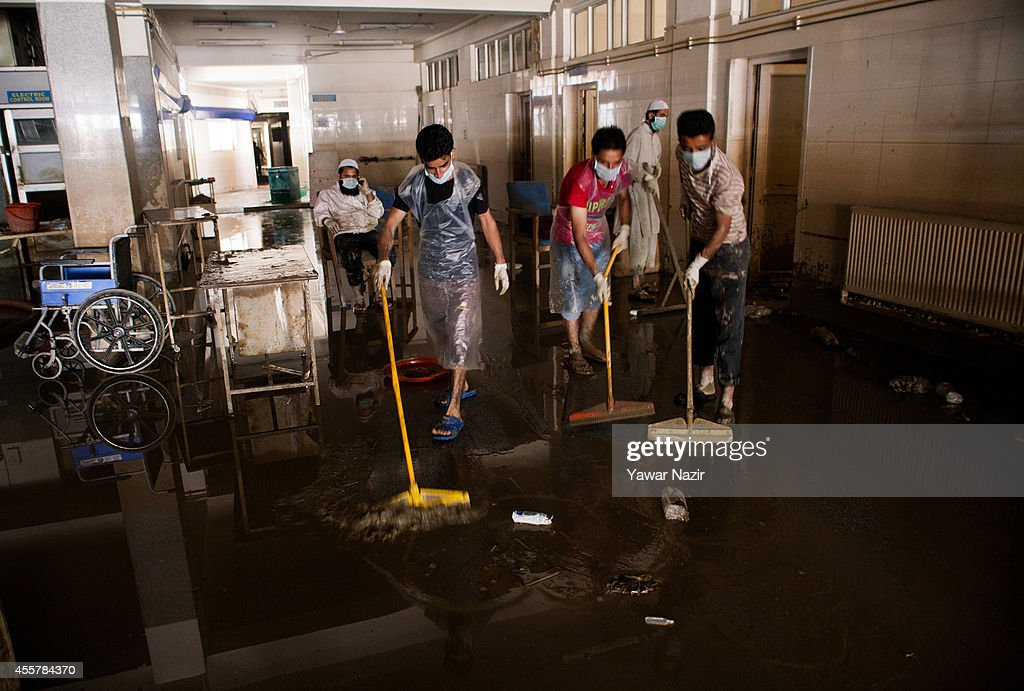 Kashmiri volunteers and hospital staff members clean silt covered Shri Maharaja Hari Singh (SMHS) Hospital after the flood waters receded from the area on September 20, 2014 in Srinagar, the summer capital of Indian administered Kashmir, India. Locals and doctors had managed to evacuated hundreds non-local medical students and patients when the floods hit the hospital. Nearly 100,000 people are still marooned in the areas of the Kashmir Valley submerged in flood waters. The floods in the Himalayan region of Kashmir were believed to be the worst in decades with over 200 dead. Health experts are worried over the stagnant waters and floating carcasses of livestock could create conditions for serious outbreaks of disease.