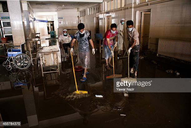 Kashmiri volunteers and hospital staff members clean silt covered Shri Maharaja Hari Singh Hospital after the flood waters receded from the area on...