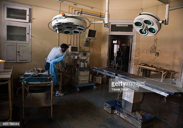 Kashmiri volunteers and hospital staff members clean silt covered operation theater and surgical equipments inside the Shri Maharaja Hari Singh...