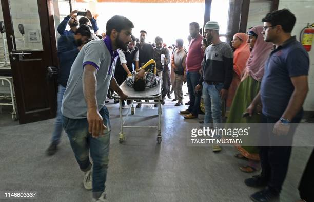Kashmiri volunteers and medical workers transport an injured youth on a stretcher after he was wounded by pellet-shot during clashes with government...
