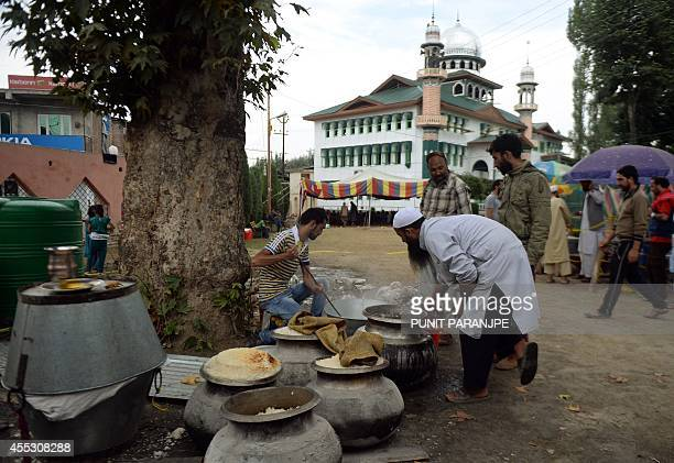 Kashmiri volunteers cook communal food for those affected by floods outside the Hyderpora mosque in Srinagar on September 12 2014 The main city in...
