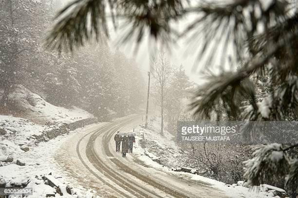 TOPSHOT Kashmiri walkers journey along a snow covered road at Gulmarg some 55kms north of Srinagar on January 3 2017 Continuing subzero temperatures...