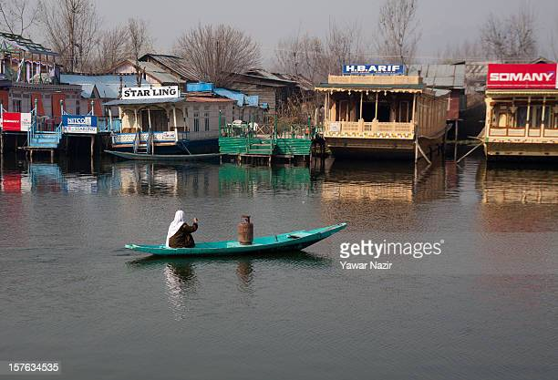 Kashmiri woman ferries gas cylinder while rowing towards her home on December 05 2012 in Srinagar the summer capital of Indian administered Kashmir...