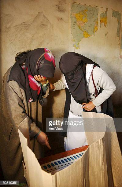 Kashmiri woman helps another cast her vote in a polling booth in Anatanag district on May 5 2004 in Indian administered Kashmir Voting in India's...