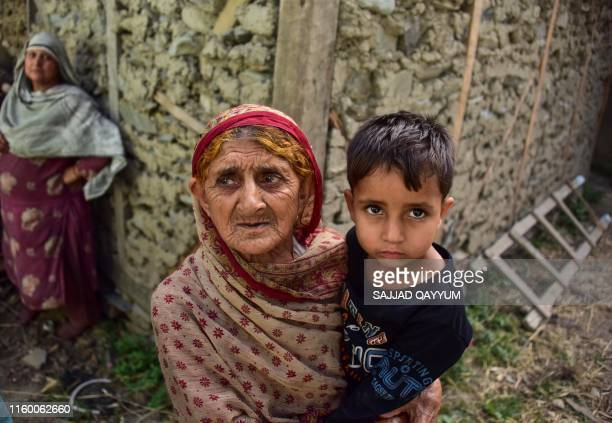 Kashmiri woman holds a child as she looks on outside her damaged house following recently cross border shelling at the Line of Control the de facto...