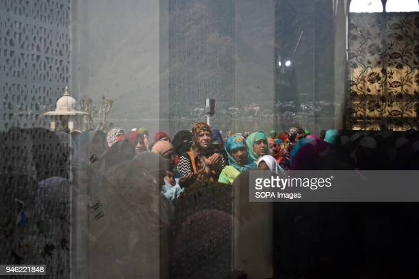 Kashmiri woman is reflected in a mirror as she prays on the occasion of the Islamic festival ShabeMeraj at Hazratbal Shrine in Srinagar Indian...