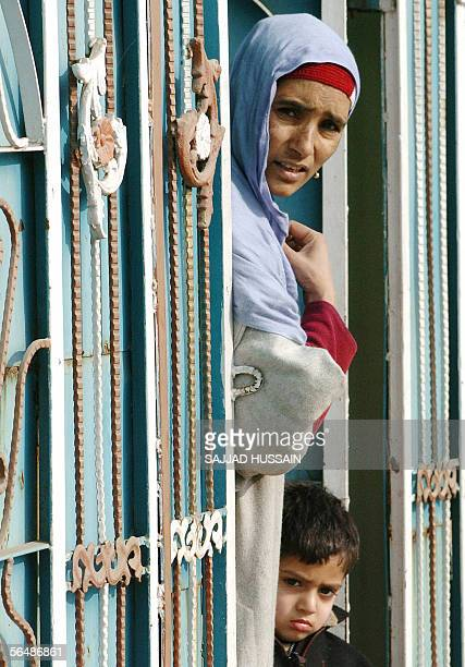 Kashmiri woman looks from a window at the scene of an encounter in which two houses were reduced to rubble during a firefight between Islamic rebels...