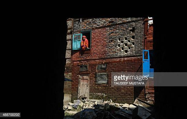 A Kashmiri woman looks out of a window of a flooddamaged house in central Srinagar on September 19 2014 The main city in Indian Kashmir has 'drowned...