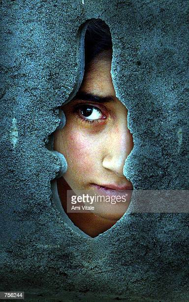 Kashmiri woman looks through a fence outside a graveyard April 3 2002 to try and see an unidentified youth who was found killed in the streets of...