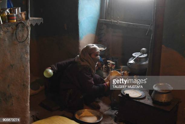 Kashmiri woman makes bread inside her home on the outskirts of Srinagar on January 17 2018 / AFP PHOTO / TAUSEEF MUSTAFA