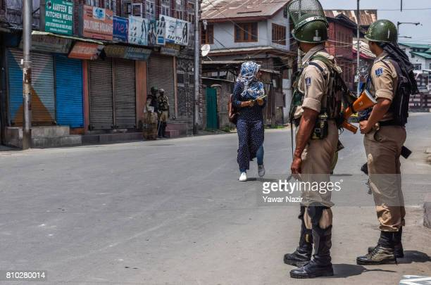 Kashmiri woman negotiates curfew as Indian paramilitary troopers stand guard ahead of the first death anniversary of Burhan Wani a young rebel...
