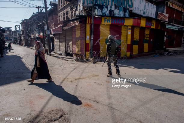Kashmiri woman negotiates curfew like restrictions as Indian government forces stand guard in the Habba Kadal on August 18 2019 in Srinagar the...