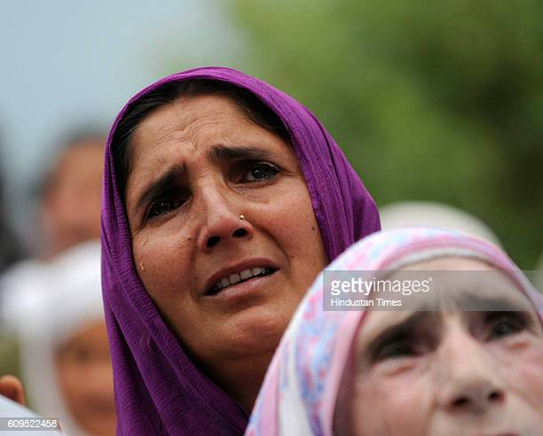 Kashmiri woman prays as a head priest displays a holy relic believed to be the hair from the beard of the Prophet Muhammad at the Hazratbal Shrine on...