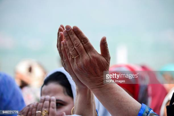 Kashmiri woman raises her hands in prayer on seeing a relic believed to be hair from the beard of Prophet Muhammad on the occasion of the Islamic...