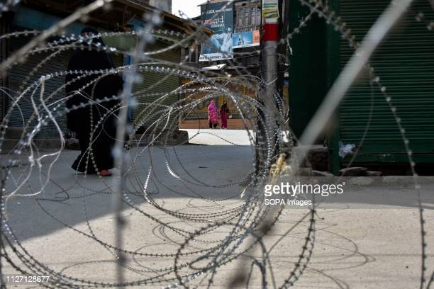 Kashmiri woman seen walking next to a barbed wire setup as a road block during restrictions in Srinagar Indian Kashmir Authorities imposed...