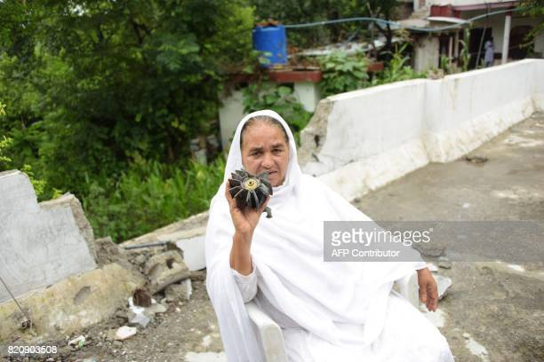 A Kashmiri woman shows a fired motor shell in front of fer damaged house after crossborder firing between Pakistan and Indian troops in Morha village...