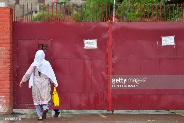 A Kashmiri woman speaks to a worker behind the door of a closed school in Srinagar on August 19 2019 Some Kashmir schools reopened on August 19 but...
