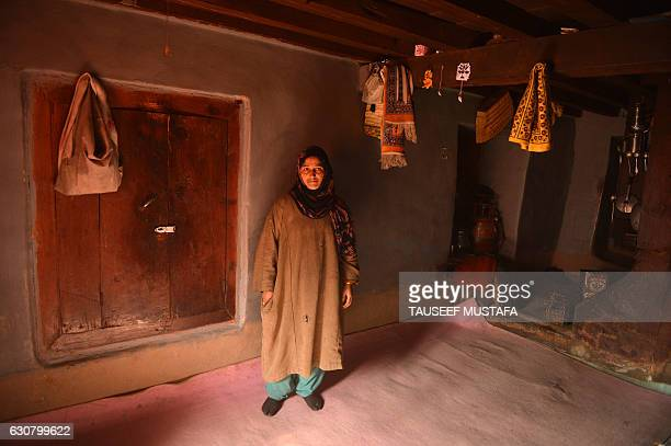 A Kashmiri woman stands inside her mud home in Kokernag some 100kms south of Srinagar on January 2 2017 A cold wave further tightened its grip in...