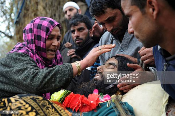 Kashmiri woman touches the face of suspected militant Bilal Ahmed Bhat during his funeral procession in the village of Karimabad in Pulwama district,...
