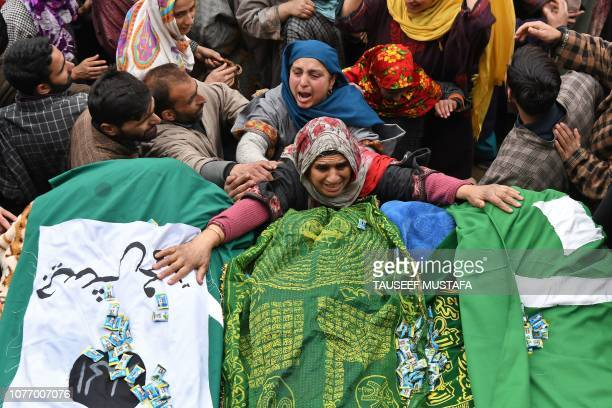 Kashmiri woman touches the feet of two slain militants during a funeral procession in Chursoo Awantipora in Pulwama district south of Srinagar on...