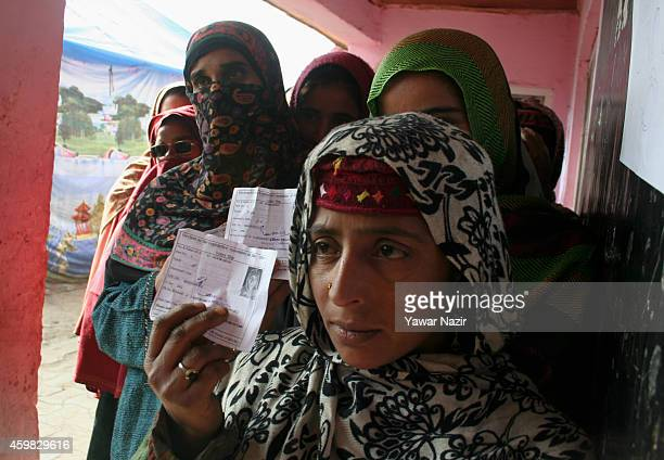 Kashmiri woman wait in queue to cast their votes outside a polling station during the second phase of assembly elections on December 02 2014 in...