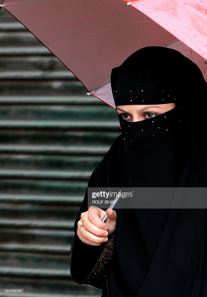 A Kashmiri woman walks through a rain shower along a street in Srinagar on May 28, 2010. Although Jhelum, the biggest river in the valley is still flowing below the danger mark, most other rivers and streams are flowing over the danger mark in both south and north Kashmir. We are closely monitoring the water levels in the Jhelum and other rivers,' said an official from the flood control department. AFP PHOTO/Rouf BHAT