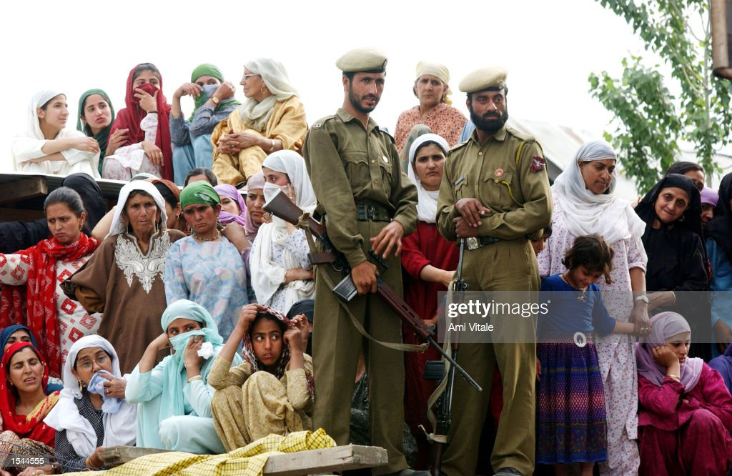 kashmiri women and police officers watch the funeral procession of