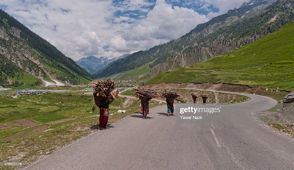 Kashmiri women carrying baskets filled with firewood, collected from the rugged mountains, as they head towards their homes on July 02, 2015 in Niligrath, some 100 km (62 miles) east of Srinagar the summer capital of Indian administered Kashmir, India.