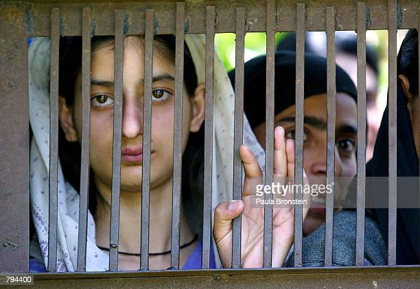 Kashmiri women look out through a gate as they watch a demonstration by the Indian Army on explosive devices in the village of Khonmon June 21 15...