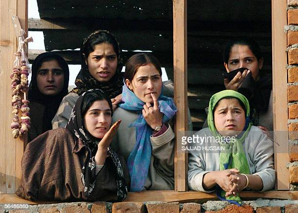 Kashmiri women looking from a window at the scene of an encounter in which two houses were reduced to rubble during a firefight between Islamic...