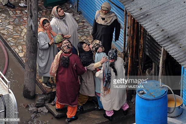 Kashmiri women react near the scene of a fire which damaged several commercial and residential buildings at Srinagar's court road business hub on...