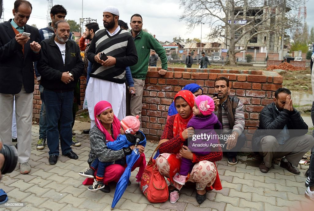 Kashmiri women sit on a pavement after they rushed out of buildings following an earthquake in Srinagar Indian controlled Kashmir on October 26 2015..