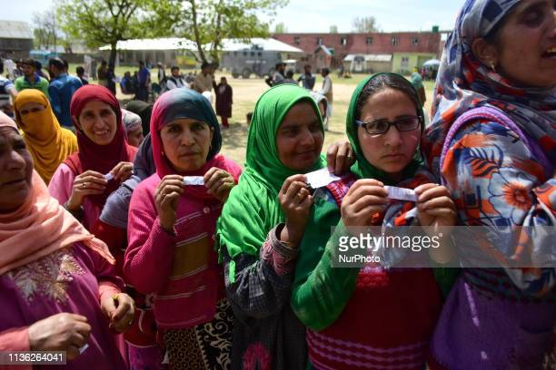 Kashmiri women stand in line show the voting slips to cast the votes outside polling booth in Shadipora area of Bandipora district during the first...